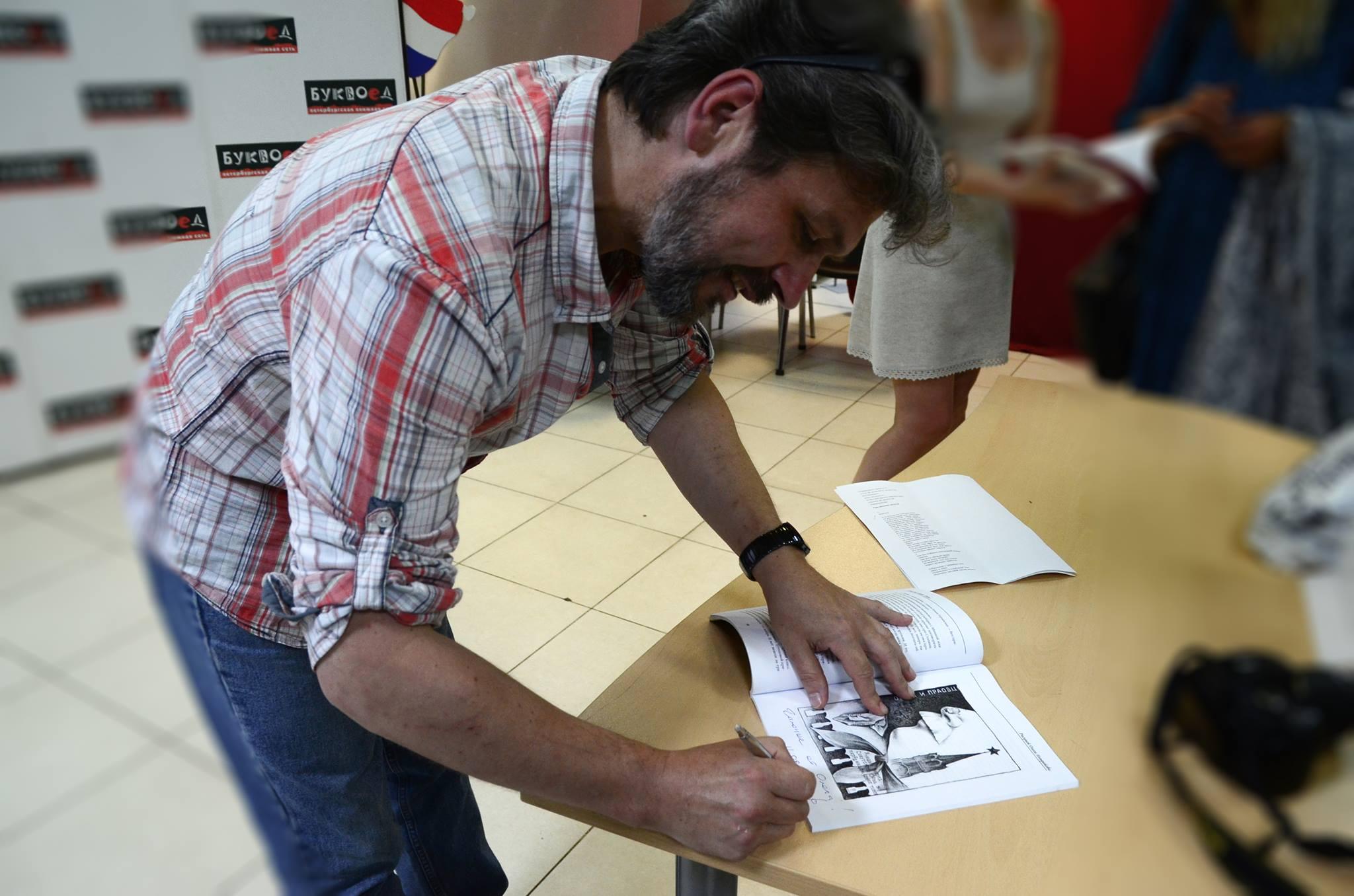 Олег Ильдюков оставляет автограф под своей иллюстрацией. Фотограф Галина Кожемяченко
