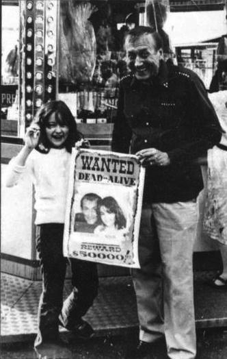 Ника с Евгением Евтушенко. На плакате надпись — Требуются мертвыми или живыми. Вознаграждение $50000. Милан, 1985